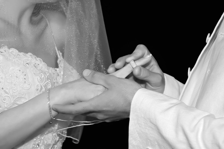 Close-up groom puts wedding ring on bride photo