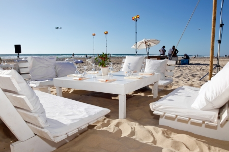 The tables are set for a romantic  wedding reception overlooking the beach and the deep blue sea