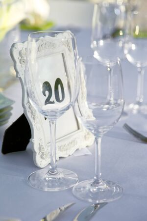 Table decorated for the wedding party, on the table is a frame with roses and a number twenty  photo