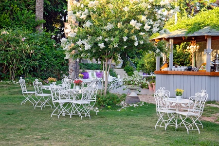 White table and chairs in beautiful garden  photo