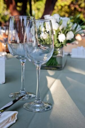 Wedding table setting with glasses of wine and white flowers photo