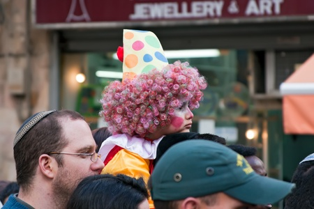 Jerusalem, Israel - 15 March 2006  Purim carnival, people watch the show   People watch the show, on the shoulders of a man sitting a child dressed in a clown  In the center of Jerusalem   Purim is celebrated annually according to the Hebrew calendar on t