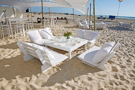 The tables are set for a romantic  wedding reception overlooking the beach and the deep blue sea   photo