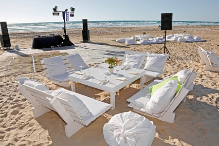 The tables are set for a romantic  wedding reception overlooking the beach and the deep blue sea  Stock Photo - 12990095