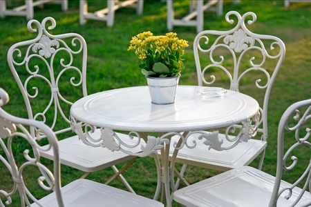 Yellow flowers in a bucket on a white table in the garden