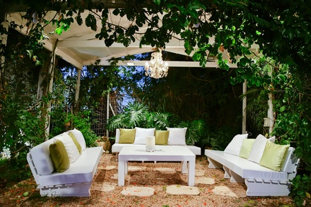 rock garden: patio romantic in the evening with benches and pillows chandelier and table