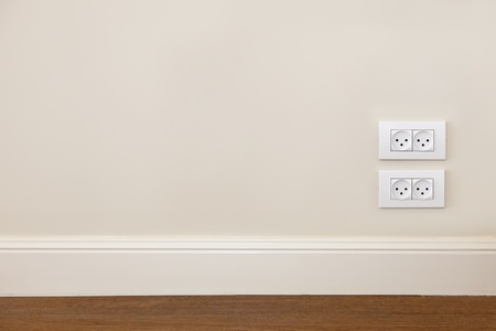 Empty wall with wooden floor and power outlet