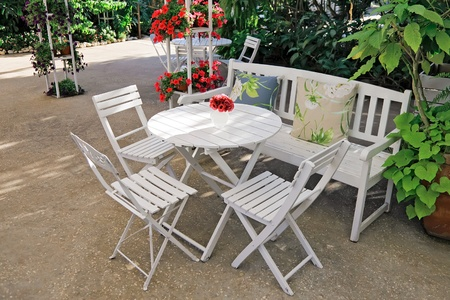 White chair, table, bench with pillows in a lush garden  Stock Photo