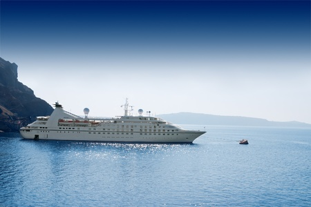 luxury liner: luxury white cruise ship on a clear day with calm seas and blue sky on the greek island of Santorini