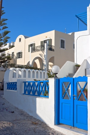 Traditional white house with blue windows on the street in Santorini, Fira, Greece  photo