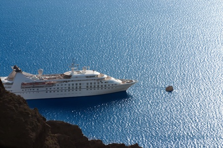 luxury white cruise ship on a clear day with calm seas and blue sky on the greek island of Santorini