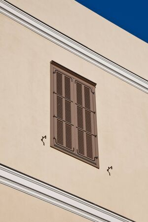 The window with wooden shutters on a beige wall   photo