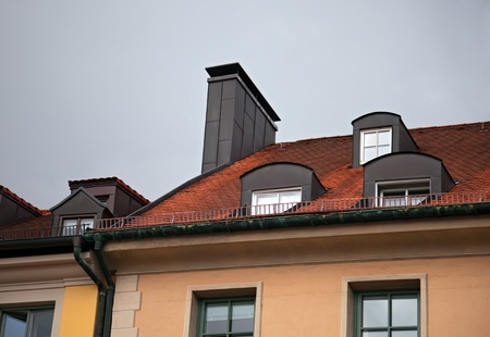 mansard: Close-up of  houses with red tile roof, chimney, attic, windows and downspout in Munich, Germany   Stock Photo