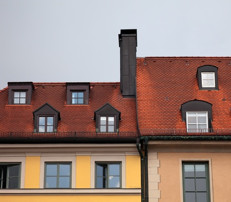 Close-up of  houses with red tile roof, chimney, attic, windows and downspout in Munich, Germany   photo