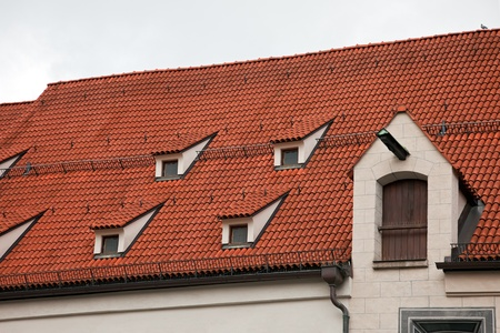 mansard: Close-up of red roof tiles with skylight in Munich, Germany