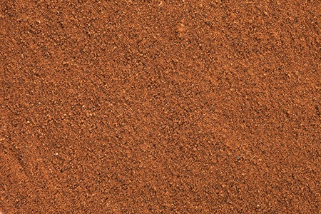 Ground Cinnamon texture, full frame background   As a spice or condiment cinnamon sold in the form of sticks or a hammer  Used as a spice in cuisines all over the world   Stock Photo