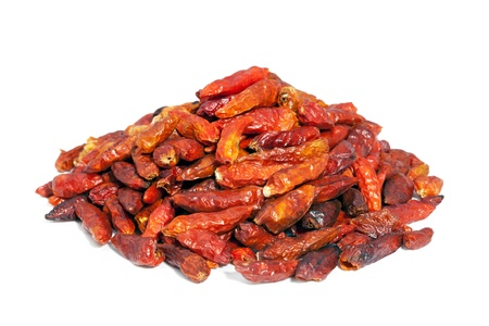 Pile dried Cayenne pepper isolated on white background  Also called Guinea spice, cow-horn pepper, aleva, bird pepper,  red pepper, hot chili pepper  Used to flavor dishes and for medicinal purposes  photo