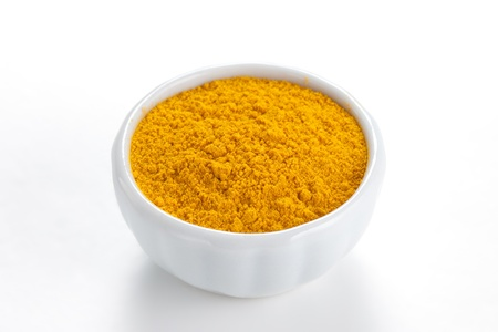 tumeric: Curry ground  Madras Curry  in a white bowl on white background  Used as a spice in cuisines all over the world  Stock Photo