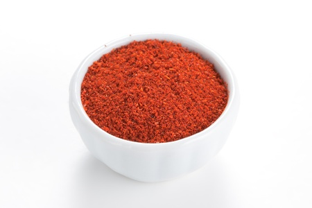 Paprika ground in a white bowl on white background  Used to color rices, stews, and soups, meats  photo