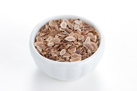 Fennel seeds  Anethum graveolens  in a white bowl on white background  The plant is used in medicine, in perfumery and cosmetics Stock Photo - 13570477