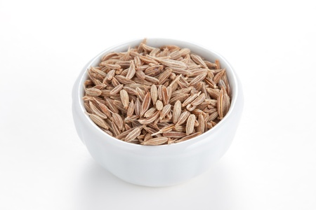 cumin: Cumin seeds in a white bowl on white background  Second most popular spice in the world after black pepper