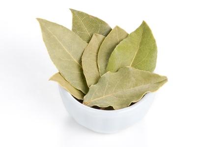 Laurierbladeren in een witte kom op een witte achtergrond wordt ook wel laurier of Laurus Nobilis gebruikt als specerij in de keuken en ook in de geneeskunde