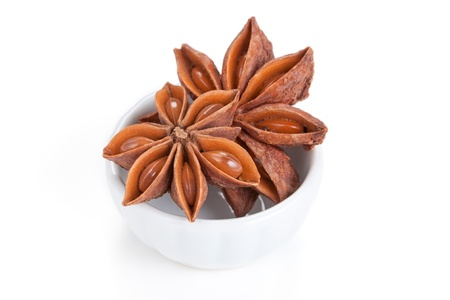 Anise star Illicium verum in a white bowl on white background Also called Star aniseed, or Chinese star anise Used as a spice in cuisines all over the world The plant is also used in medicine