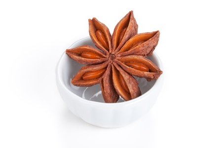 badiane: Anise star  Illicium verum   in a white bowl on white background  Also called Star aniseed, or Chinese star anise  Used as a spice in cuisines all over the world  The plant is also used in medicine  Stock Photo