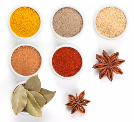 Different spices in white bowls isolated on white background  Paprika, Curry, Black Pepper, Ginger, Cinnamon, Bay Leaves