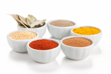 Different spices in white bowls isolated on white background  Paprika, Curry, Black Pepper, Ginger, Cinnamon, Bay Leaves  photo