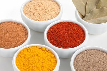 flavoring:  Different spices in white bowls isolated on white background  Paprika, Curry, Black Pepper, Ginger, Cinnamon, Bay Leaves