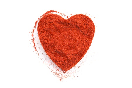 Pile of ground Paprika isolated in heart shape on white background