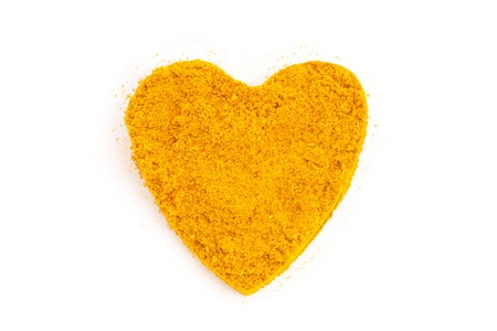 Heap ground Curry  Madras Curry  isolated in heart shape on white background photo