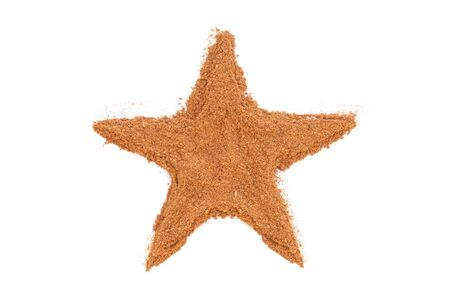 Heap of ground Cinnamon isolated in star shape on white background photo