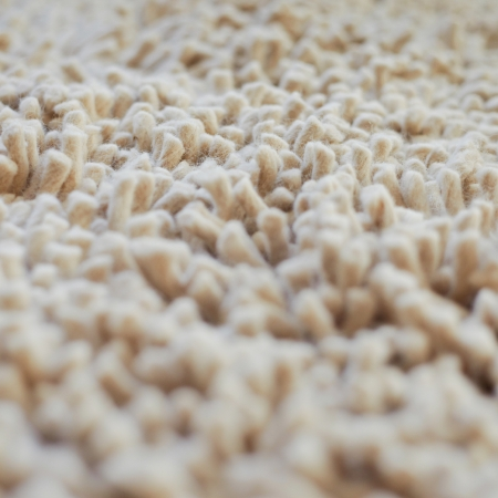Cream coloured carpet background, close up photo