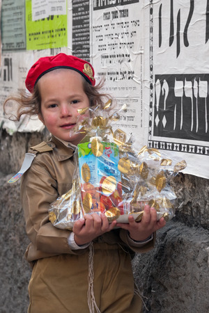 street party: JERUSALEM, ISRAEL - MARCH 15, 2006: Purim carnival in the famous ultra-orthodox quarter of Jerusalem - Mea Shearim. Portrait of a boy children dressed in carnival costumes soldier. In his hand mishloach manot. Purim is celebrated annually according to the