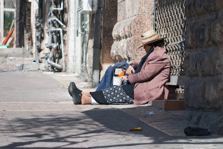 mea shearim: JERUSALEM, ISRAEL - MARCH 15, 2006: Purim carnival in the famous ultra-orthodox quarter of Jerusalem - Mea Shearim. Woman tramp begging. On his head wearing a straw. Purim is celebrated annually according to the Hebrew calendar. Purim is the custom of mas Editorial