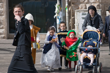 shearim: JERUSALEM, ISRAEL - MARCH 15, 2006: Purim carnival. Ultra Orthodox  woman with children crossing the road.Children dressed in costumes. In the famous ultra-orthodox quarter of Jerusalem - Mea Shearim. Purim is celebrated annually according to the Hebrew c