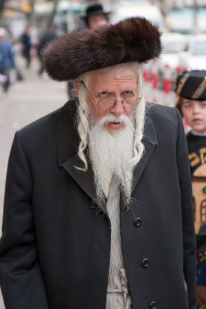 jewish quarter: JERUSALEM, ISRAEL - MARCH 15, 2006: Purim carnival in the famous ultra-orthodox quarter of Jerusalem - Mea Shearim. Portrait of  men dressed in traditional Jewish clothing. On his head wearing a cap. Purim is celebrated annually according to the Hebrew ca Editorial