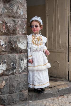 annually: JERUSALEM, ISRAEL - MARCH 15, 2006: Purim carnival in the famous ultra-orthodox quarter of Jerusalem - Mea Shearim. Portrait of young girl dressed in a princess costume. Purim is celebrated annually according to the Hebrew calendar. Purim is the custom of Editorial