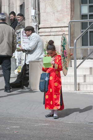 mea shearim: JERUSALEM, ISRAEL - MARCH 15, 2006: Purim carnival in the famous ultra-orthodox quarter of Jerusalem - Mea Shearim. Portrait of young girl dressed in a costume chinese woman. Purim is celebrated annually according to the Hebrew calendar. Purim is the cust Editorial