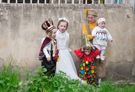 jewish ethnicity: JERUSALEM, ISRAEL - MARCH 15, 2006: Purim carnival in the famous ultra-orthodox quarter of Jerusalem - Mea Shearim. Group portrait of five children dressed in carnival costumes. Purim is celebrated annually according to the Hebrew calendar. Purim is the c