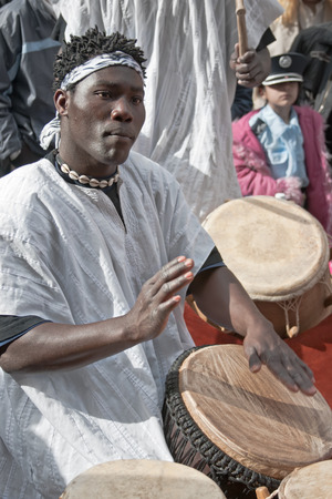 masquerading: JERUSALEM, ISRAEL - MARCH 15, 2006: Purim carnival, street musician playing the tam-tam drums. Purim is celebrated annually according to the Hebrew calendar. Purim is the custom of masquerading in costume and the wearing of masks.