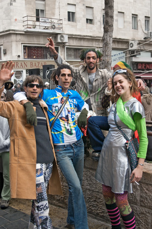 masquerading: JERUSALEM, ISRAEL - MARCH 15, 2006: Purim carnival. Group of people celebrate the festival. Three young men and a young girl.Dressed in colorful costumes. Purim is celebrated annually according to the Hebrew calendar. Purim is the custom of masquerading i