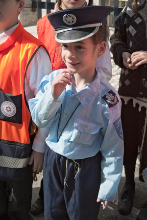 mea: JERUSALEM, ISRAEL - MARCH 15, 2006: Purim carnival in the famous ultra-orthodox quarter of Jerusalem - Mea Shearim. Portrait of a boy children dressed in carnival costumes police. In his hand a cigarette. Purim is celebrated annually according to the Hebr