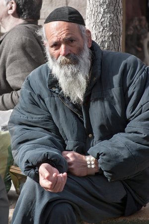 kippah: JERUSALEM, ISRAEL - MARCH 15, 2006: Purim carnival. Portrait of a tramp begging. An elderly man in a black jacket, kippa and beard. Purim is celebrated annually according to the Hebrew calendar. Purim is the custom of masquerading in costume and the weari
