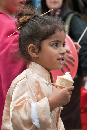 masquerading: JERUSALEM, ISRAEL - MARCH 15, 2006: Purim carnival. Portrait of a little girl dressed in a suit Japanese. Girl eating ice cream. Purim is celebrated annually according to the Hebrew calendar. Purim is the custom of masquerading in costume and the wearing