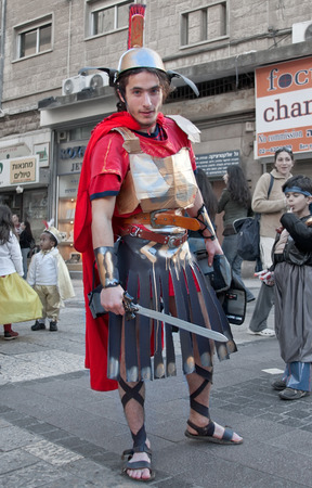 masquerading: JERUSALEM, ISRAEL - MARCH 15, 2006: Purim carnival. A young man dressed in a suit of a Roman soldier with a sword in his hand. Purim is celebrated annually according to the Hebrew calendar. Purim is the custom of masquerading in costume and the wearing of