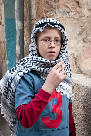 shearim: JERUSALEM, ISRAEL - MARCH 15, 2006: Purim carnival in the famous ultra-orthodox quarter of Jerusalem - Mea Shearim. Portrait of a boy children dressed in carnival costumes arab. In his hand a cigarette. Purim is celebrated annually according to the Hebrew Editorial