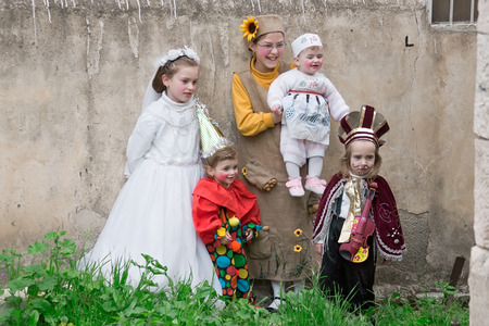 mea: JERUSALEM, ISRAEL - MARCH 15, 2006: Purim carnival in the famous ultra-orthodox quarter of Jerusalem - Mea Shearim. Group portrait of five children dressed in carnival costumes. Purim is celebrated annually according to the Hebrew calendar. Purim is the c